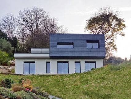 Une maison ardoise à flanc de colline au-dessus de la mer